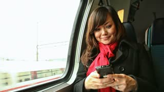 Young Asian woman texting with her smartphone as she travels by train