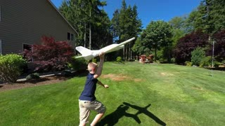 Young boy tossing a toy model airplane to his father at home in the back yard