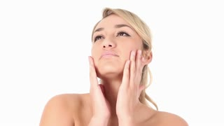 Young Hispanic woman rubbing moisturizer on her face