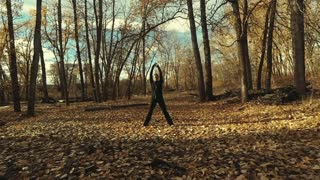 Young woman performing warm-up stretches outdoors before taking her morning run