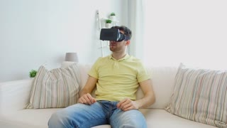 3d technology, entertainment and people concept - young man with virtual reality headset playing video game at home