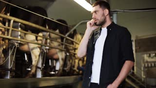 agriculture industry, farming, technology, people and animal husbandry concept - young man or farmer calling on cellphone and cows in cowshed on dairy farm