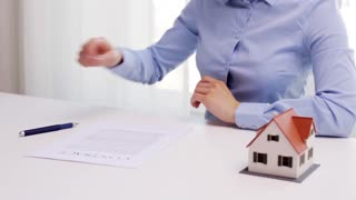 architecture, building, business, real estate and people concept - woman with house model and pen signing contract document at office