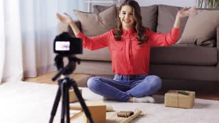 blogging, christmas, technology, mass media and people concept - happy smiling woman or blogger with camera recording tutorial video about gift wrapping at home
