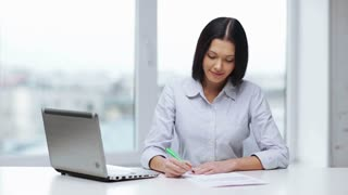 business and education concept - woman with documents and pen filling form