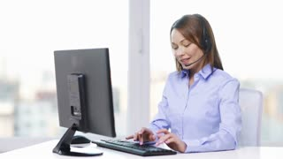 business and office concept - smiling female helpline operator with headphones and computer at office