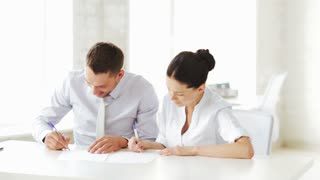business and office - man and woman signing a contract