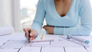 business, architecture, building, construction and people concept - architect woman measuring blueprint with compass and writing dimensions to notebook