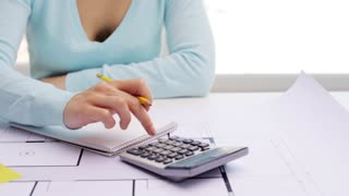 business, architecture, building, construction and people concept - architect woman with blueprint counting on calculator and writing to notebook