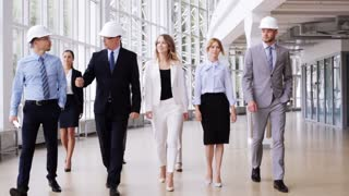 business, architecture, construction, teamwork and people concept - happy group of architects in helmets with blueprint walking along at office building