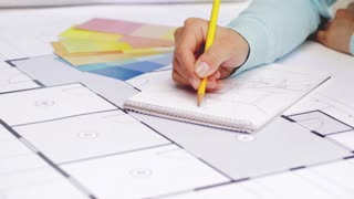 business, architecture, design and people concept - woman designer with blueprint drawing to notebook