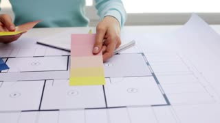 business, architecture, interior design and people concept - woman with house blueprint and swatches choosing color