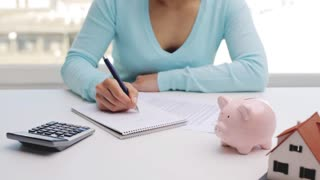 business, architecture, real estate and people concept - woman with house model, piggy bank and notebook counting on calculator