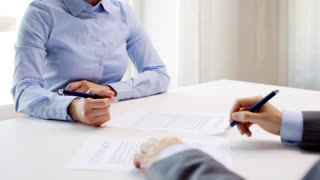 business, cooperation, partnership, deal and people concept - man and woman signing contract and shaking hands at office