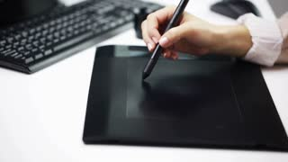 business, creativity, people and technology concept - woman or designer hand drawing with stylus on pen tablet at office