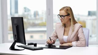 business, creativity, people and technology concept - young businesswoman or graphic designer with computer drawing on pen tablet at office