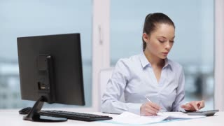 business, education and technology concept - concentrated businesswoman with computer, papers and calculator in office