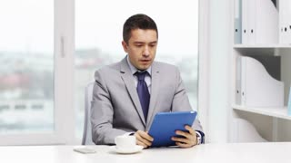 business, education, people and technology concept - displeased businessman with tablet pc and coffee in office