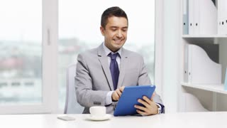 business, education, people and technology concept - smiling businessman with tablet pc computer and coffee in office