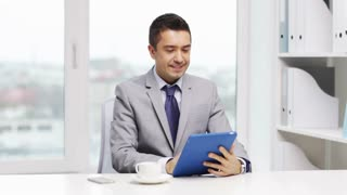 business, education, people and technology concept - smiling businessman with tablet pc computer drinking coffee in office