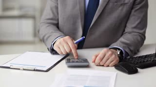 business, finances, people, technology and office work concept - close up of businessman with papers and calculator