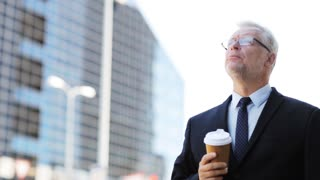 business, hot drinks, break and people and concept - senior businessman drinking coffee from disposable paper cup on city street