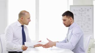 business, partnership, finances and office concept - two serious businessmen holding papers and talking in office