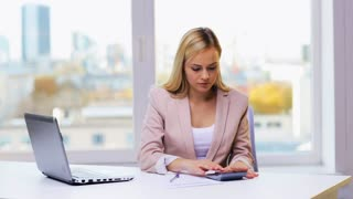 business, people, accounting and technology concept - businesswoman with laptop, calculator and papers working in office