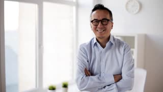 business, people and gesture concept - happy smiling asian businessman showing thumbs up at office