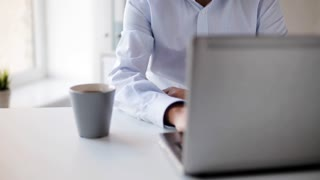 business, people and technology concept - businessman in eyeglasses with laptop computer drinking coffee or tea at office