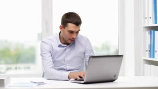 business, people and technology concept - businessman with laptop computer calling on smartphone in office