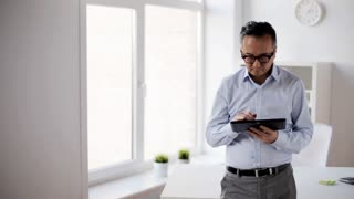 business, people and technology concept - businessman with tablet pc computer in office