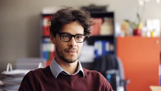 business, people, emotion and facial expression concept - smiling young man in eyeglasses at office