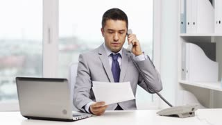 business, people, paperwork and technology concept - angry businessman with laptop computer and papers calling on phone in office