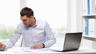 business, people, paperwork and technology concept - busy businessman with laptop computer, calculator and papers counting finances in office