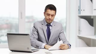 business, people, paperwork and technology concept - disappointed businessman with laptop computer and papers working in office
