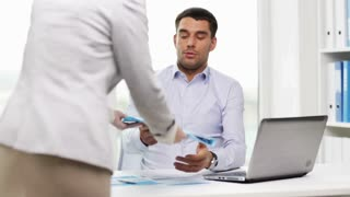 business, people, paperwork and technology concept - secretary or assistant and businessman with laptop computer looking at papers in office