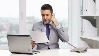 business, people, paperwork and technology concept - smiling businessman with laptop computer and papers calling on phone in office