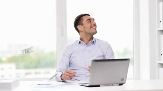business, people, success and fortune concept - happy businessman with dollar money and laptop computer sitting at table in office