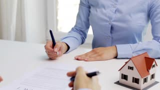 business, real estate, deal and people concept - man and woman with house model and pen signing contract document and shaking hands at office