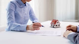 business, real estate, deal and people concept - man giving house keys to woman after signing contract document at office