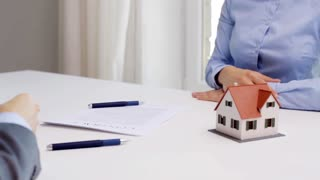 business, real estate, deal and people concept - man giving house keys to woman at office