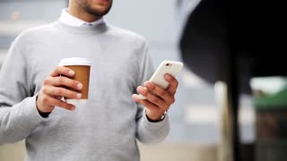 business, technology and people concept - young man with smartphone drinking coffee from paper cup on city street