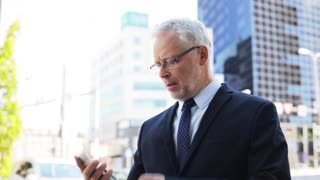 business, technology, communication and people concept - senior businessman calling on smartphone and checking time in city