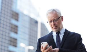 business, technology, communication and people concept - senior businessman calling on smartphone and checking time on his wristwatch in city