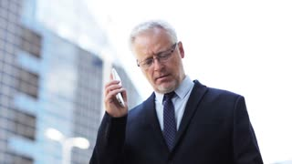 business, technology, communication and people concept - senior businessman calling on smartphone in city