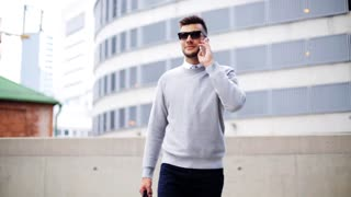 business, technology, communication and people concept - young man in sunglasses with bag calling on smartphone and walking along city street