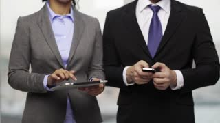 business, technology, internet and office concept - businessman and businesswoman with smartphone and tablet pc computer