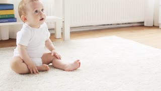 childhood, babyhood and people concept - happy little baby crawling to sofa and getting up in living room at home