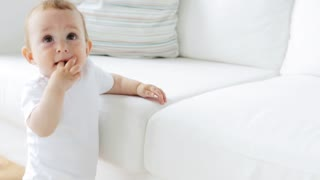 childhood, babyhood and people concept - happy little baby standing and holding to sofa in living room at home